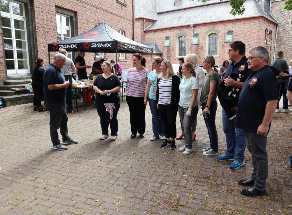 Tenor Drummer Hubert übergibt im Namen der Blatzheim Highlanders die Spende an die Organisatorinnen von Blatzheim hilft!